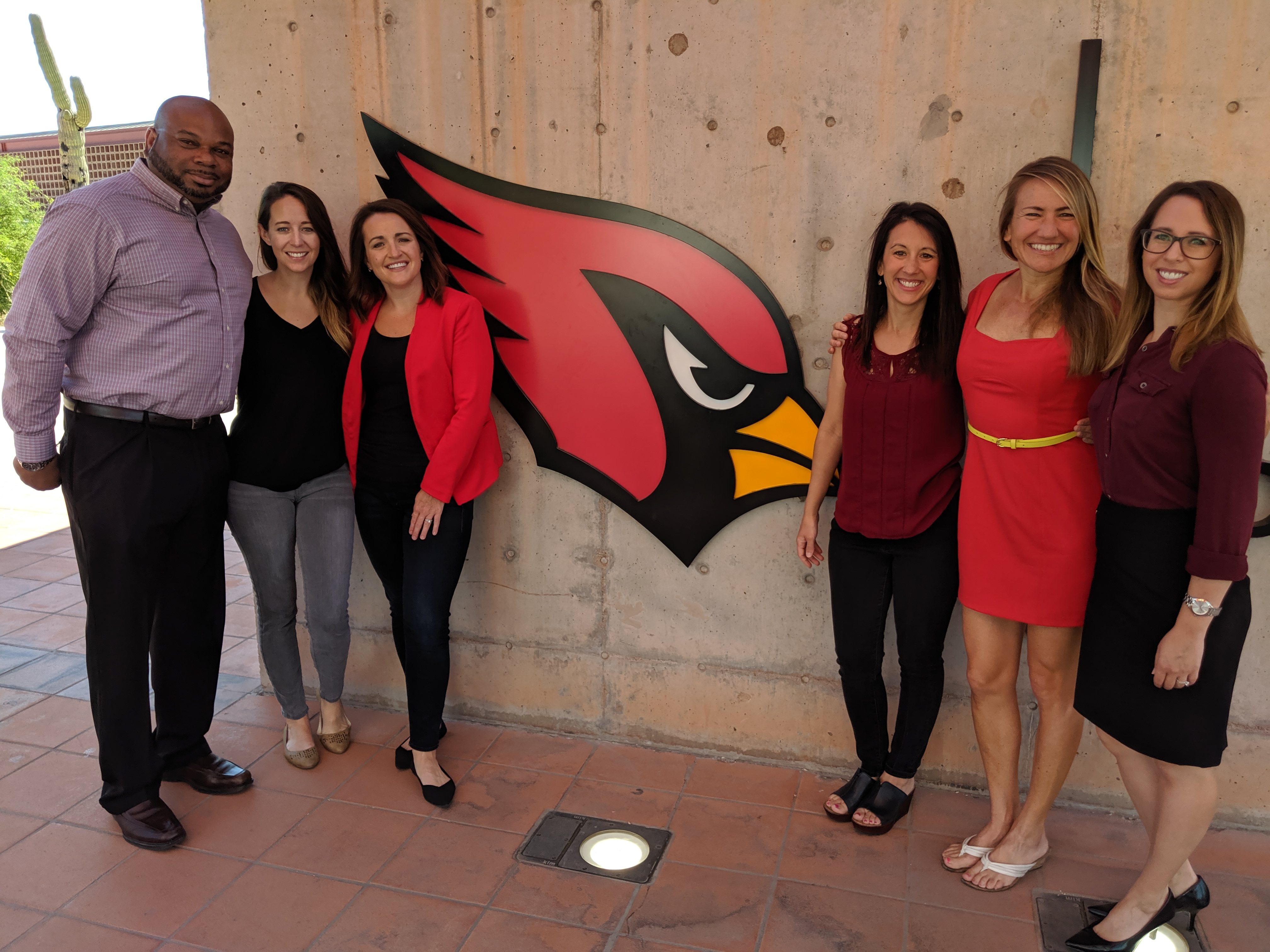 Arizona Justice Project staff members stand outside the Arizona Cardinals office next to the Cardinals logo.